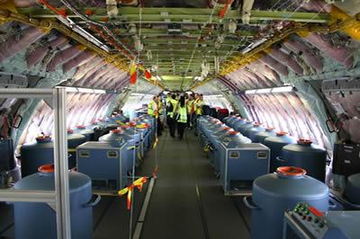 Interno di aereo caricato con taniche per irrorazione