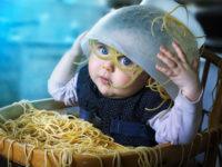 Bambino con spaghetti in testa