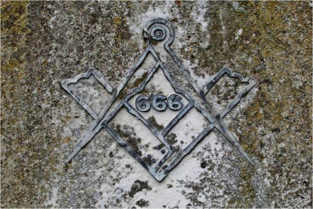 I simboli massonici di squadra e compasso con al centro il numero della bestia in una formella